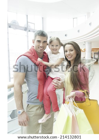 Father holding young girl posing with mother in shopping mall - stock photo