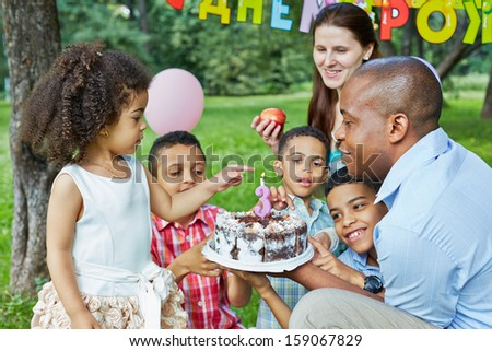 Father holds birthday cake with burning candle on it, little daughter and her three brothers finger cake, mother looks at them