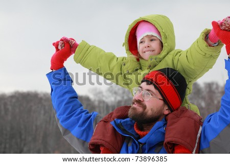 Father holds daughter on shoulders and glad - stock photo