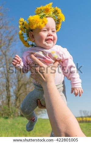 Father holds his baby. Happy baby has dandelion wreath on her head. - stock photo