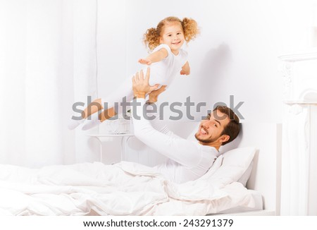 Father holds his daughter with her hands apart - stock photo