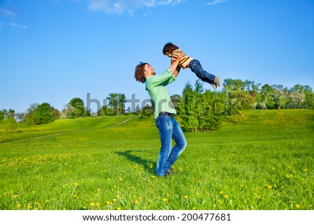 Father holds kid up above him in the air - stock photo