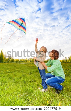 Father holds kid while watching flying kite - stock photo