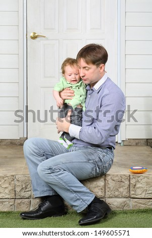 Father holds on hands crying baby, soothes and sits on steps near door. - stock photo
