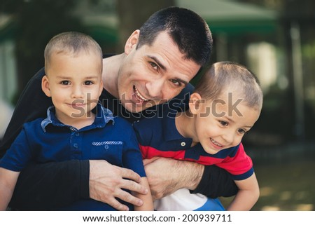 Father hugging his two beautiful sons outdoor in a park. - stock photo