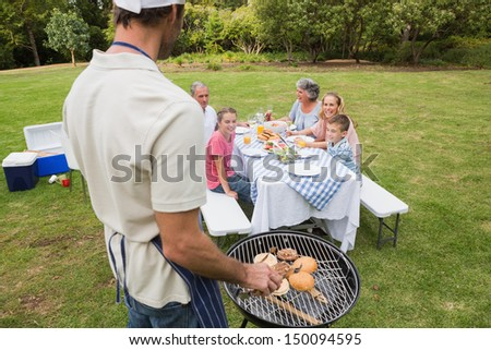 Father in chefs hat and apron cooking barbecue for his family sitting at picnic table - stock photo