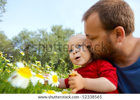 father in early thirties gives his son a kiss on the cheek in the flower field - stock photo