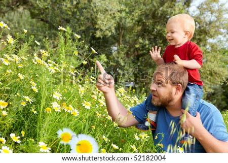 father in his early thirties shows his happy toddler son a flower in the spring meadow - stock photo