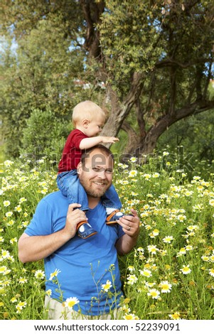 father in his early thirties smiles with his toddler son on the shoulders in the spring flowers meadow - stock photo