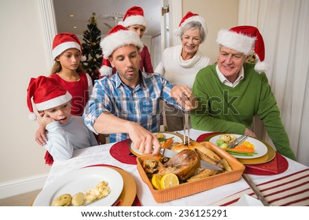 Father in santa hat carving chicken during dinner at home in the living room - stock photo