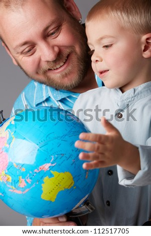father in thirties and toddler boy of three years old learning geography with an earth globe - stock photo