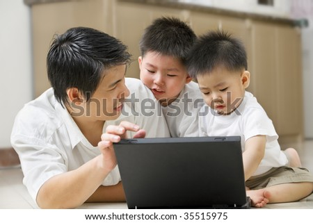 Father introduce technology to his sons using laptop in home - stock photo