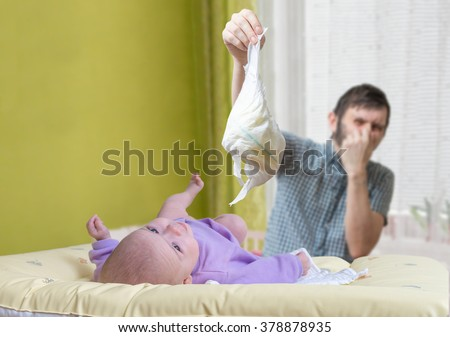 Father is changing stinky diapers. Care of baby with diarrhea. - stock photo