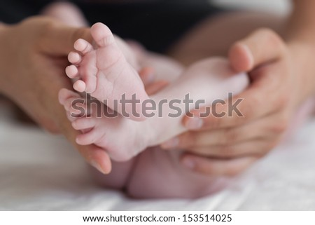 Father is gently holding his baby feet - stock photo