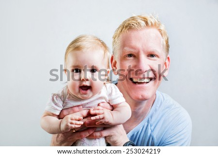 Father is having fun with his little baby - stock photo
