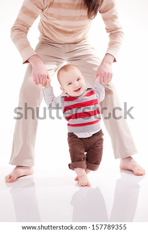 Father is helping her son to make first steps - stock photo
