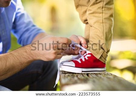 Father is helping his son to tie his shoes in summer nature - stock photo