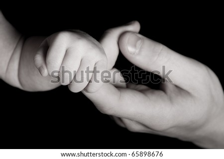 Father is holding little baby hand to be safe - stock photo