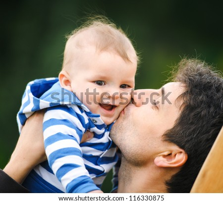 Father is kissing his son - stock photo