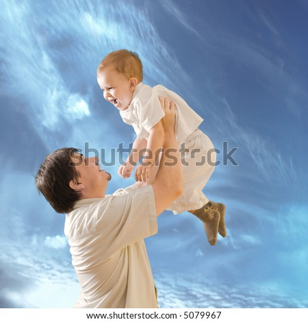 Father is lifting 2 years old baby boy. - stock photo
