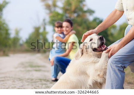 Father is playing with dog in the nature. Beautiful mother and her daughter are looking at them with joy. They are embracing and smiling on background. Focus on animal - stock photo
