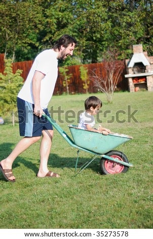 Father is playing with kid driving him on green meadow - stock photo