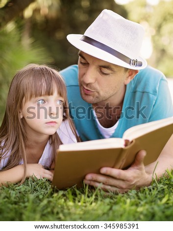 Father is reading a book to his daughter outdoors - stock photo