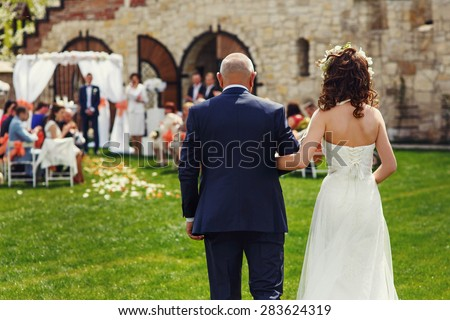father is taking his stylish young happy daughter to the altar - stock photo
