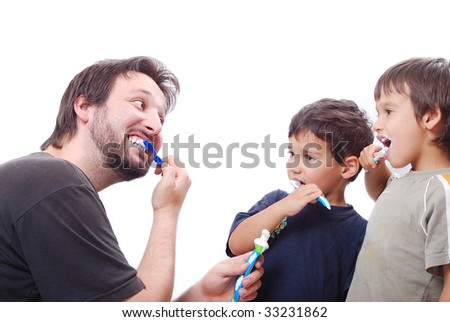Father is teaching his sons hot to clean the teeth properly - stock photo