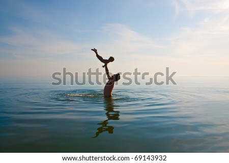 father is tossing up a child in water - stock photo
