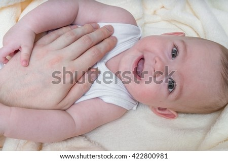 Father is touching his child with hand. Happy baby is smiling.