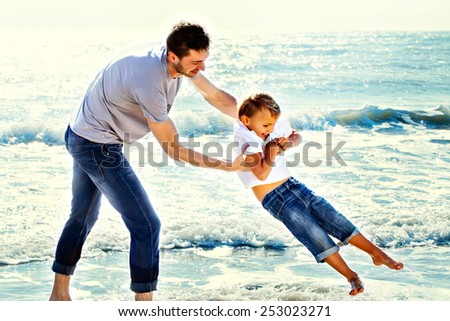 father jokes affectionately with his son at sea - stock photo