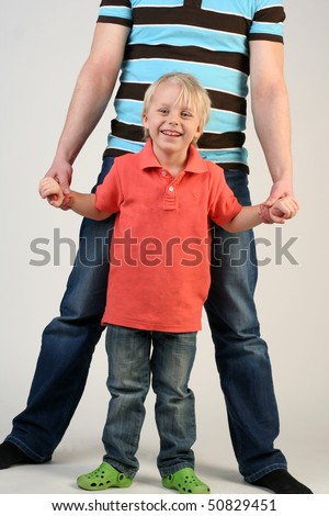 Father keeping smiling son's hands in studio
