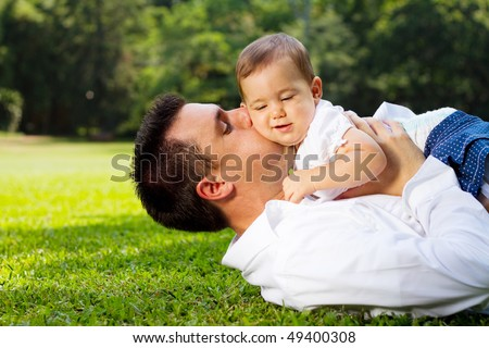 father kissing daughter outdoors - stock photo