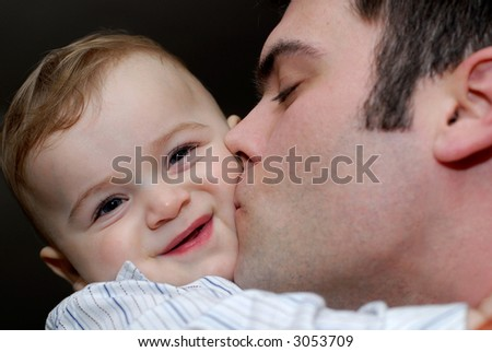 father kissing his baby son
