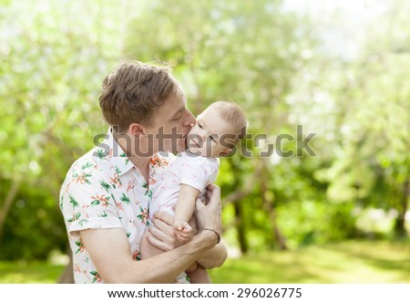 Father kissing his cute baby  outdoors in spring park against natural green background. family shot  - stock photo