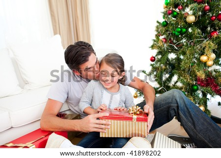 Father kissing his little daughter after giving her a Christmas gift at home