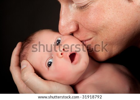 Father kissing his twenty days old newborn baby - stock photo