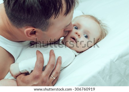 father kissing his two months old baby, in bed at home - stock photo
