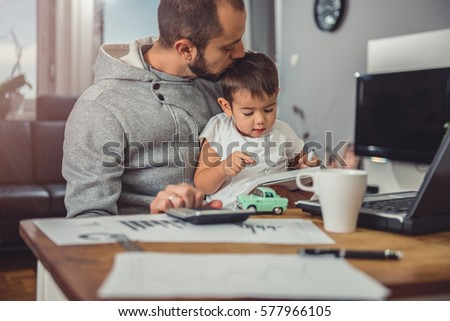 Father kissing son at home office