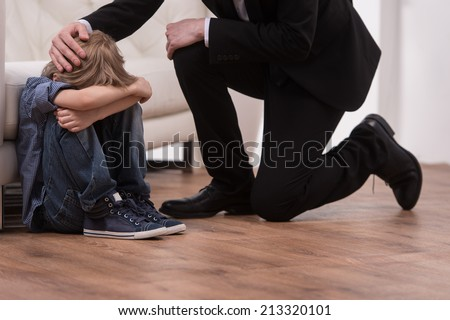 Father kneeling and comforts sad child. boy sitting on floor in bedroom and crying - stock photo