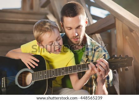 father learning his boy to play guitar, they sit on the steps of a country house on a warm summer evening. - stock photo