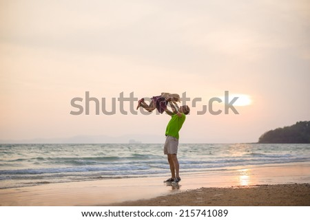 Father lift up daughter on hands on sunset ocean beach with yacht on back - stock photo