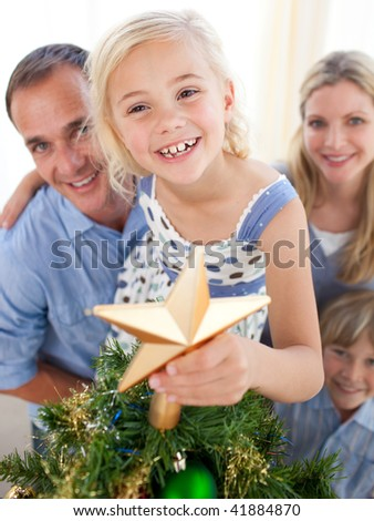 Father lifting his daughter to put the Christmas star on top of the tree at home - stock photo