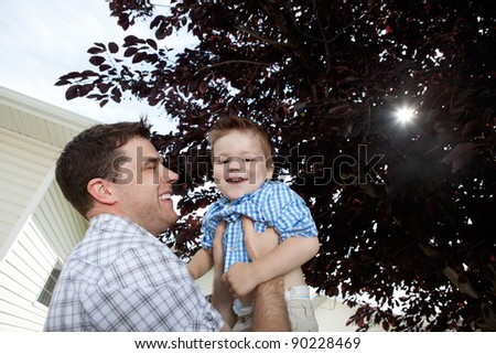 Father lifting his little adorable boy - stock photo