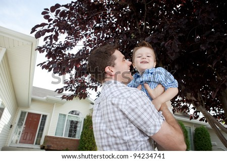 Father Lifting His Little Adorable Boy In Front Of House. - stock photo