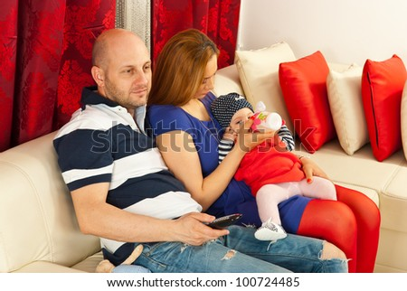 Father looking at tv and mother feeding baby and sitting together on couch in their living room - stock photo