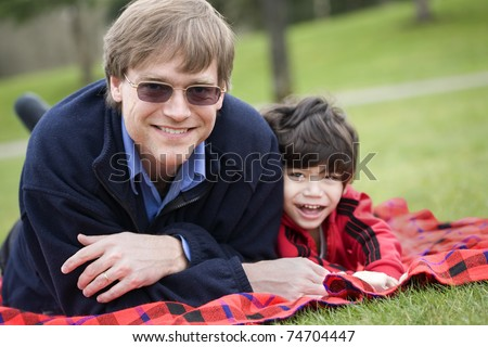 Father lying on blanket with disabled son at park - stock photo