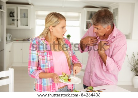 Father making teenage daughter do chores at home - stock photo