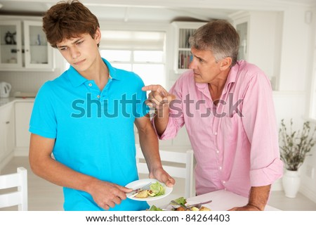 Father making teenage son do housework - stock photo